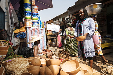 Woman choosing wooden bowl at market stall in Accra, Ghana, Africa