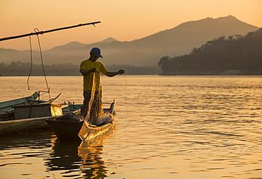 Man reeling in fishing net on Mekong River, Luang Prabang, Laos, Indochina, Southeast Asia, Asia