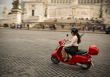 Young woman riding Vespa moped through streets in front of Vittorio Emanuele Monument, Rome, Lazio, Italy, Europe