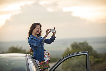 Young woman taking picture with her phone, Mineral de Pozos, Guanajuato, Mexico, North America