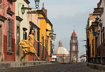 Young woman dancing down cobbled street (recreo), San Miguel de Allende, Guanajuato, Mexico, North America