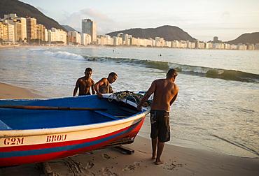 Fishermen taking their boat out at dawn, Copacabana, Rio de Janeiro, Brazil, South America