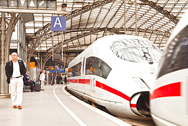 Passengers waiting to board a highspeed ICE train in Cologne railway station, North Rhine-Westphalia, Germany, Europe