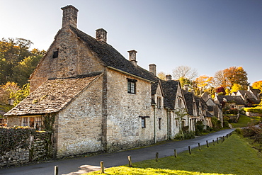 The midday sun casts its light across a row of medieval houses at Arlington Row, Bibury in Gloucestershire, Cotswolds, England, United Kingdom, Europe