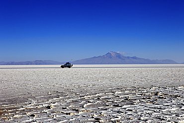 A 4x4 on Salar de Uyuni, the largest salt flat in the world, South West Bolivia, Bolivia, South America
