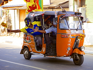 Sri Lankan cricket supporters driving along in a Tuk tuk (rickshaw) during the cricket World Cup final 2011, Sri Lanka, Asia