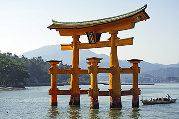 Tourist passing through the floating red wooden torii gate of Miyajima, Itsukushima, UNESCO World Heritage Site, Hiroshima Prefecture, Honshu, Japan, Asia