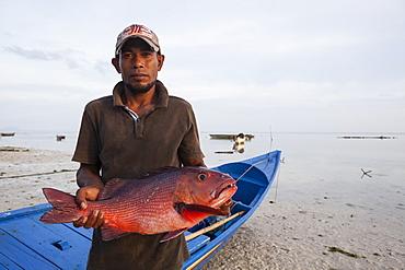 Fisherman showing a fish - Grogos Island Maluku Indonesia