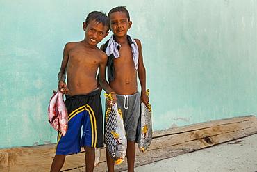 Children carrying Fishes - Grogos Island Maluku Indonesia