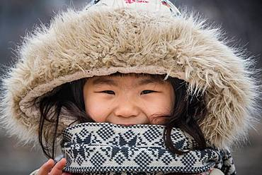 Korean teenager in Seoul street in winter, wearing a hat