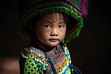 Vietnamese girl at Sapa covered market in Northern mountains. She is dressed in the traditional clothes of Hmong flowers.