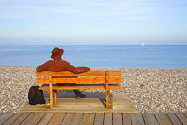 Walker sitting on a bench and looking at the sea on which a sailboat sails on the horizon, on a pebble beach in Cayeux-sur-Mer, Picardy, France.