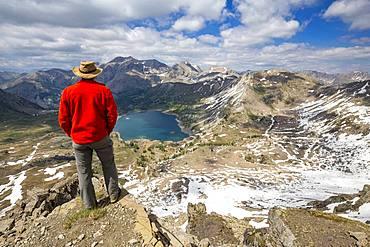 Hiker on the Tours du Lac, Lake Allos (2226 m) and in the background Mont Pelat (3051m), Haut-Verdon, Mercantour National Park, Alps, France