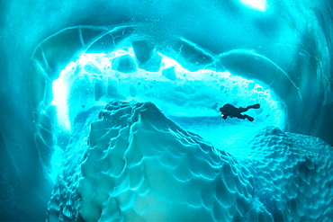 Only in springtime, when the hard winter slowly subsides, are the ice-cold waters suitable for divers who can dive around a iceberg that floats in crystal-clear water, Tasiilaq, East Greenland