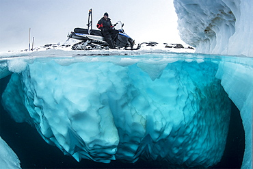 Split image of guide with snowmobile waiting the divers, only in springtime, when the hard winter slowly subsides, are the ice-cold waters suitable for divers who can dive around a iceberg that floats in crystal-clear water, Tasiilaq, East Greenland