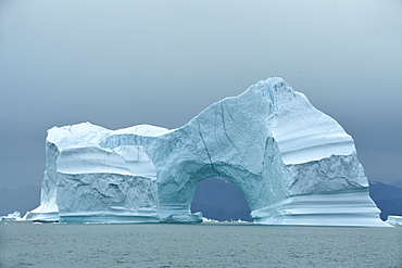 Arch in an iceberg in Scoresbysund, North East Greenland