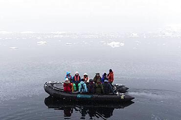 Tourist in inflatable boat, Wilhelmina Bay, Antarctica.