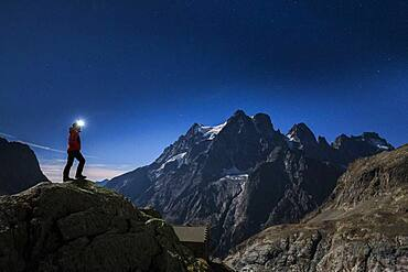Mount Pelvoux (3932m) and the Pelvoux glacier illuminated by a full moon night, hiker at the Glacier Blanc refuge (2580m), Vallouise valley, Brian?onnais region, Ecrins National Park, Hautes-Alpes, France