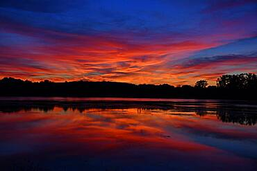 Paquis pond at sunset, reflections on the water, Brognard, Doubs, France