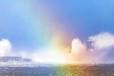 Waves hitting the lighthouse of the Carnot dike with a rainbow created by reflection of light on the waves, during the storm Ciara, Boulogne sur mer, February 2020, Hauts de France, France