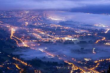 Fog at dusk in the morning over the Arve valley. Air and light pollution in the Arve valley. Shooting from Mont M?le, Haute-Savoie, France