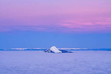 Mole Mountain emerges from a sea of clouds at morning twilight. Shooting from the Flaine station. Haute-Savoie, France In the background, the Jura chain.