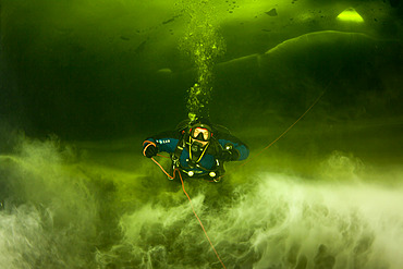 Scuba diver under ice in a halocline cloud, a subtype of chemocline caused by a strong, vertical salinity gradient within a body of water. Arctic circle Dive Center, White Sea, Karelia, northern Russia