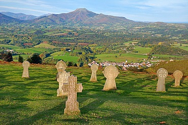 Granite discoid steles overlooking the village of Ainhoa (most beautiful village in France). In the distance, the Rhune mountain located on the border ridge between France and Spain, Basque Country, France