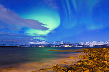 meteorology northern lights over landscape coast with mountains snow covered sky with stars