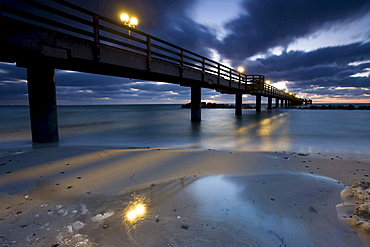 beach with pier of Wustrow at dusk sunset Baltic Sea sky with clouds mood Mecklenburg-Vorpommern Germany