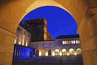 Porta nigra with archway and fountain court illuminated at night