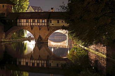 old historical bridge with houses crossing river Pegnitz illuminated at night Nuremberg francs Germany