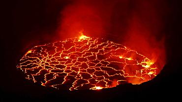 volcano Nyiragongo crater with lava fountains in the lava lake rising smoke nature natural phenomenon night view