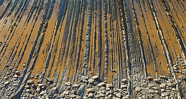 parallel rock formations on sea shore in tidal zone of sea bird's eye view outdoors La Rasa Mareal flysch cliffs Basque Country Spain Europe