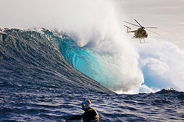 A helicopter filming a tow, in surfer at Peahi Jaws off Maui Hawaii The head in the foreground is driving a jetski