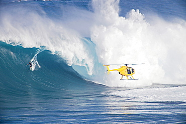 A helicopter filming a tow, in surfer at Peahi Jaws off Maui Hawaii
