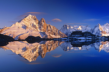 scenic view of rocky mountain peaks covered with snow and mountain hut with reflection in lake under blue sky outdoors horizontal format reflect reflecting reflections reflected sunlight sunlit Les Drus Les Aiguilles Lac Blanc near Chamonix French Alps France Europe