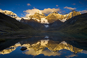 Andes mountains mountain Yerupaja 6635 m and Yerupaja Chico 6121 m partially covered with snow mountain lake in front with water surface reflection sunrise natural mood