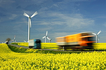 energy wind energy wind turbines and street with traffic through rape field landscape