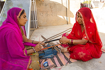 Women constructing solar cookers at the Barefoot College in Tilonia, Rajasthan, India. The Barefoot College is a worldwide charity, founded by Bunker Roy, its aims are, education, drinking water, electrification through solar power, skill development, health, women empowerment and the upliftment of rural people.