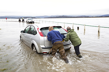 A motorist stuck in flood waters on the road at Storth on the Kent Estuary in Cumbria, UK, during the January 2014 storm surge and high tides, is pushed out by two helpers.