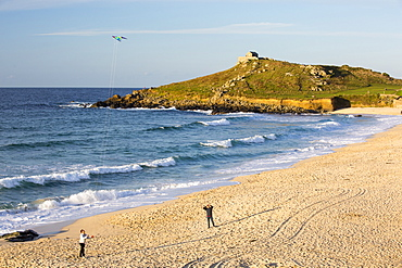 St Ives head from Porthmeor beach in St Ives, Cornwall, UK, with a couple flying a kite on the beach.