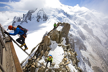 Mont Blanc from the Aiguille Du Midi above Chamonix, France, with climbers on the Cosmiques Arete, climbing the ladder to access the cable car station.
