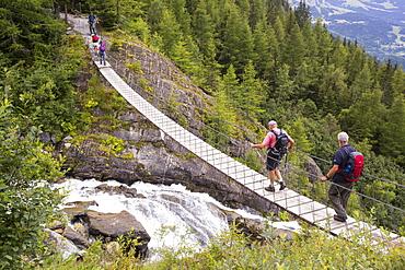 Walkers on the Tour Du Mont Blanc cross a suspension bridge across the meltwater river from the Bionnassay glacier;