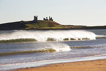Spray in windy conditions from breaking waves, looking towards Dunstanburgh Castle, Northumberland, UK.