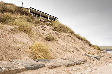 A holiday chalet in the sand dunes at low Newton by the Sea on Northumberland's coast stands precarioulsy close to the edge following a severe storm surge in December 2013 that caused considerable erosion to the sand dunes.