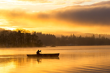 Sunrise over Lake Windermere in Ambleside, Lake District, UK, with a man paddling a Canadian Canoe.