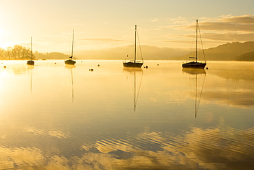 Sunrise over sailing boats on Lake Windermere in Ambleside, Lake District, UK.