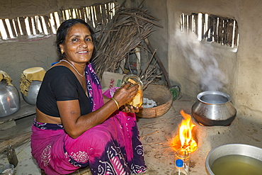 A villager woman in a remote subsistence farming village on an island in the Sunderbans, the Ganges Delta in Eastern India that is very vulnerable to sea level rise. She is cooking on a traditional clay oven, fuelled by biofuel (rice stalks), low carbon cooking.