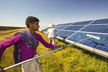 Asia's largest solar popwer station, the Gujarat Solar Park, in Gujarat, India. It has an installed capacity of 1000 MW. Here workers wash dust off the panels to increase their efficiency.